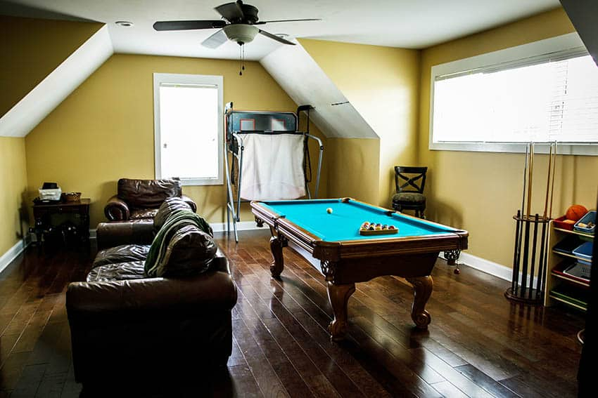 Attic man cave with hardwood floors pool table leather couches