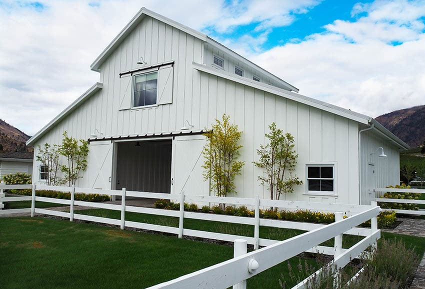 2 story barn home kit with white siding and fencing