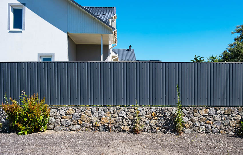 Corrugated metal fencing above rock wall around house