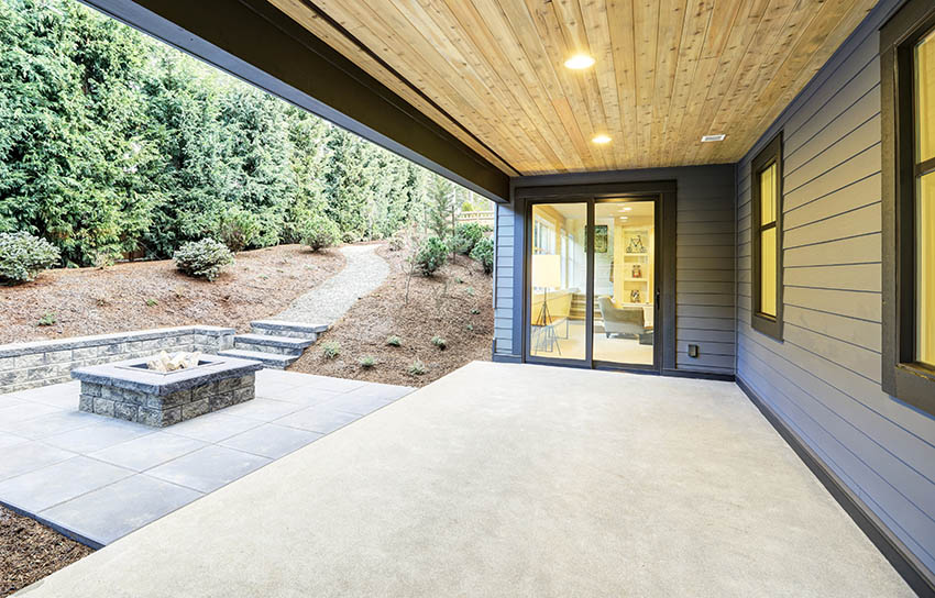 Covered polished concrete patio next to regular cement patio with fire pit