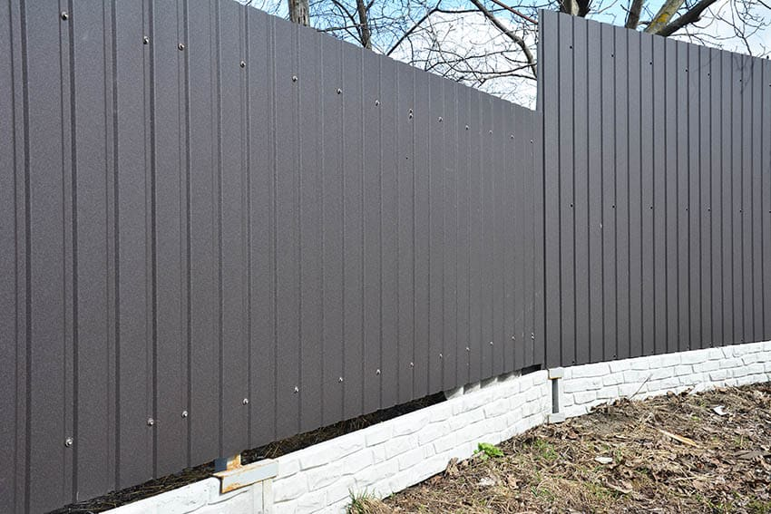 Gray metal corrugated fence panels