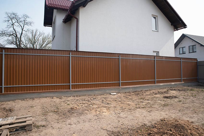Home backyard with brown corrugated metal fence with steel supports
