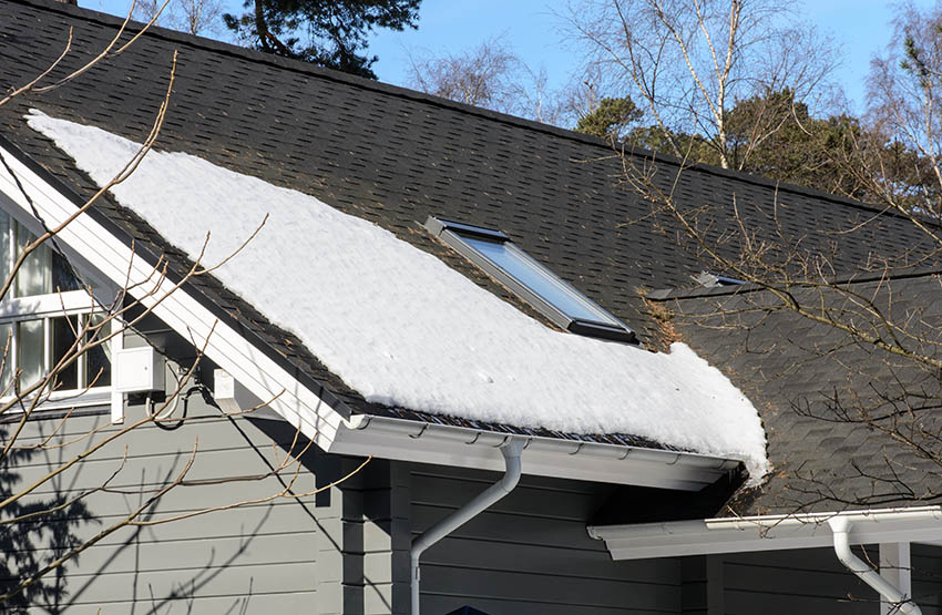 Hot black roof shingles melting snow