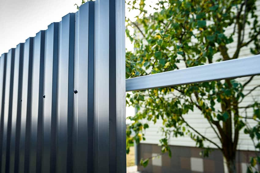 Installing gray corrugated metal fencing