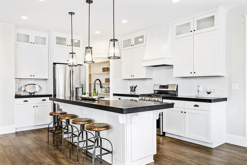 Kitchen with black laminate countertops white shaker cabinets wood plank flooring pendant lights