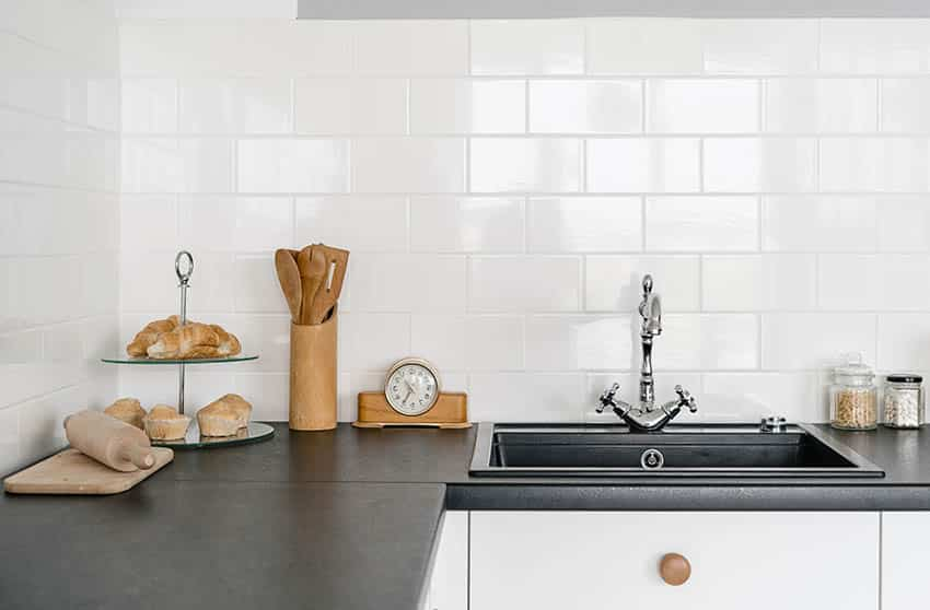 Kitchen with black leathered countertop white subway tile