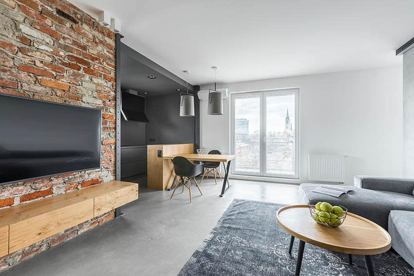 Living room with grey polished concrete flooring rough brick accent wall area