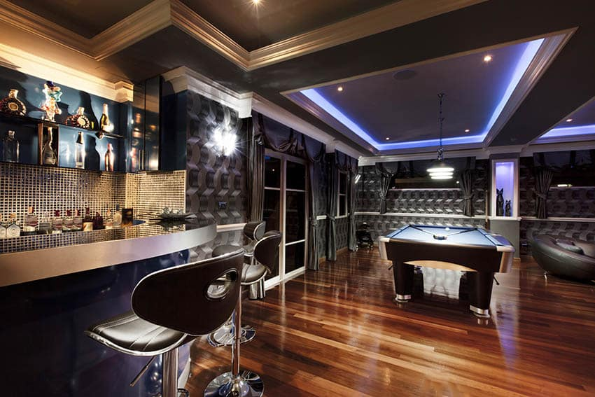 Man cave with cherry hardwood floors home bar pool table tray ceiling lighting