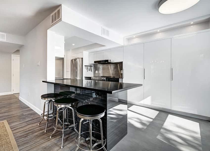 Modern kitchen with black laminate countertop peninsula white gloss cabinets