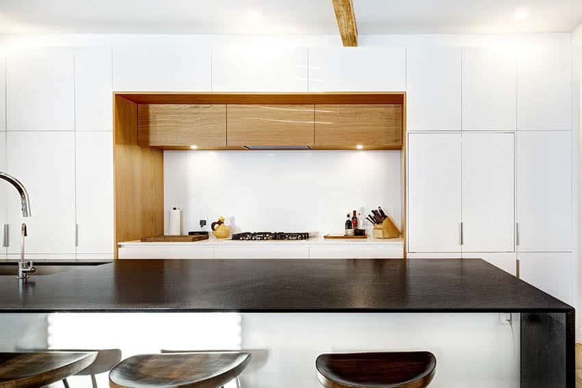 Modern kitchen with black leathered granite countertops gloss white cabinets