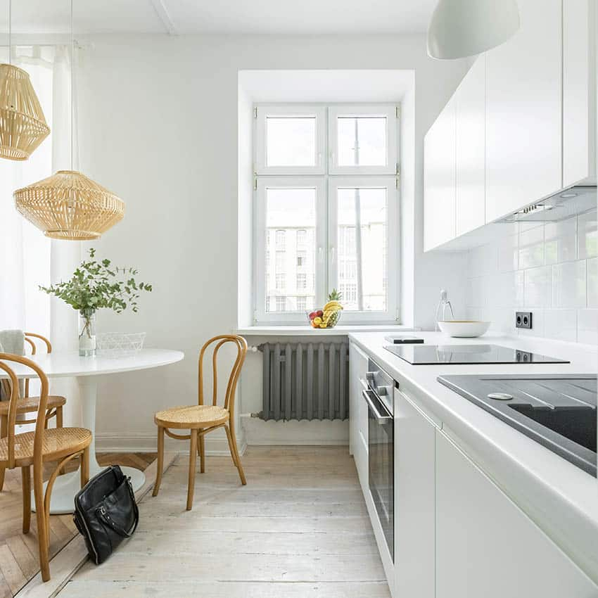 One wall kitchen with white laminate countertops white washed wood flooring