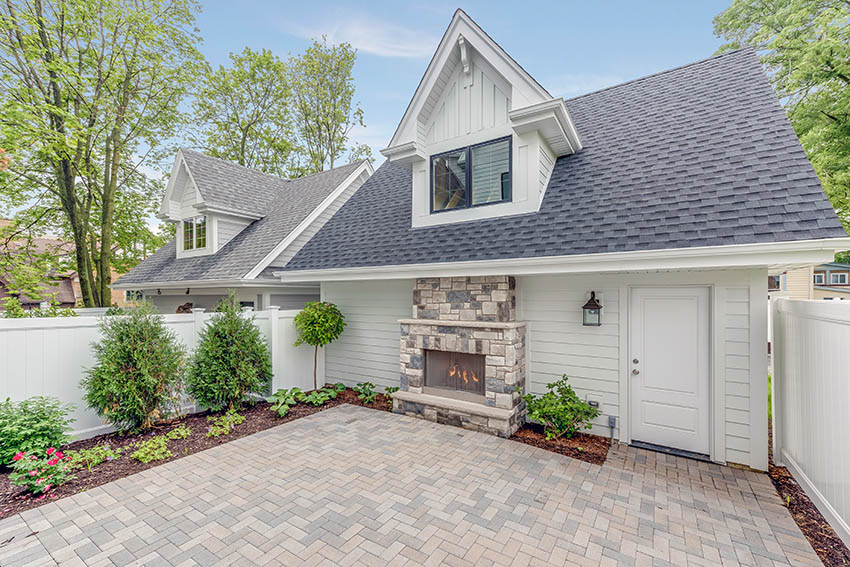 Paver patio with fireplace landscaped backyard