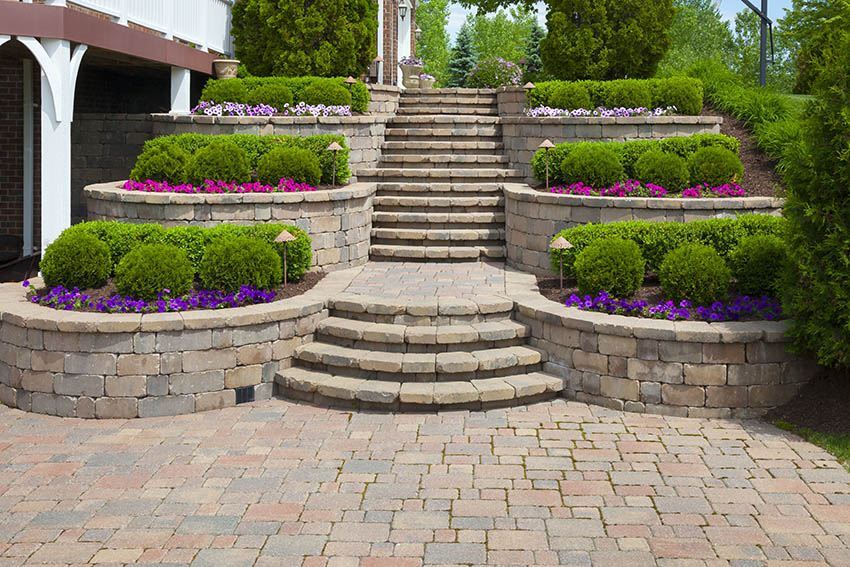 Paver patio with retaining wall and colorful flowers