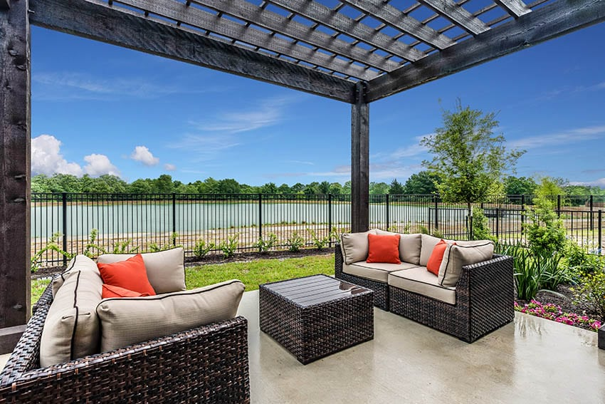 Polished concrete patio with wood pergola black metal fence waterfront views