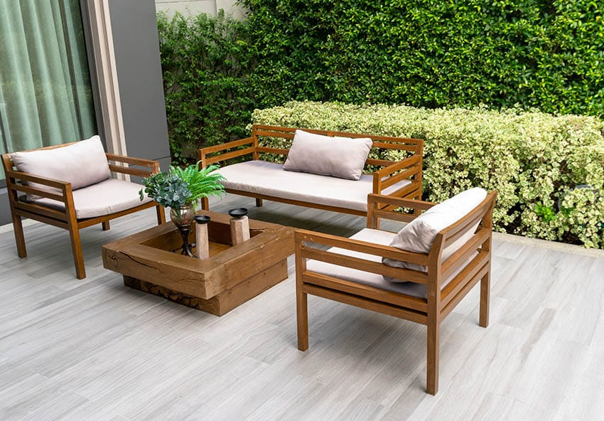 Porcelain tile outdoor patio with acacia wood furniture chairs and loveseat