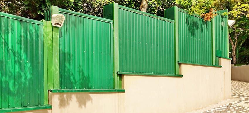 Sloped corrugated metal fence on concrete
