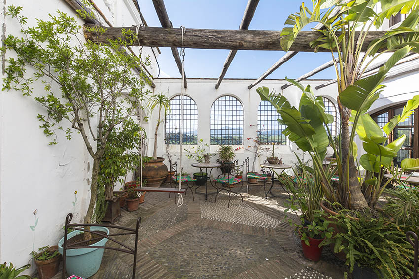 spanish style patio with curved windows and metal lattice security fence