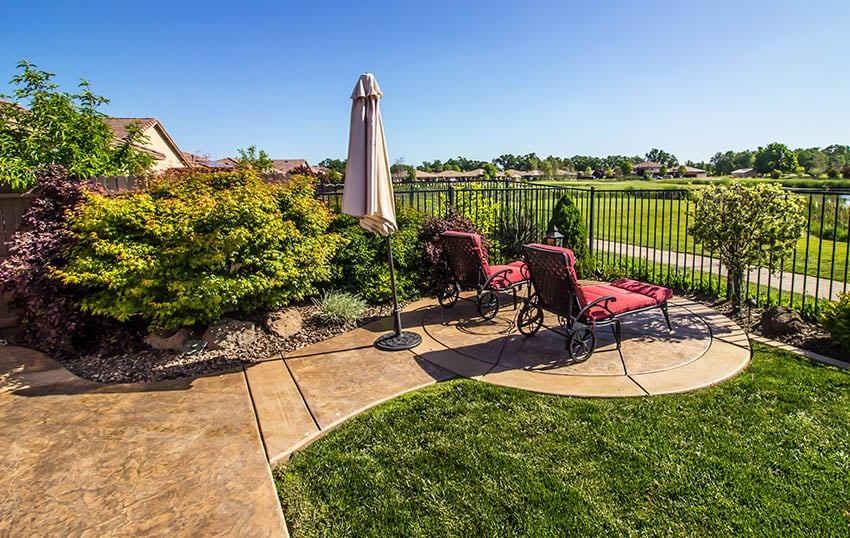 Stained stamped concrete patio with circular sitting area