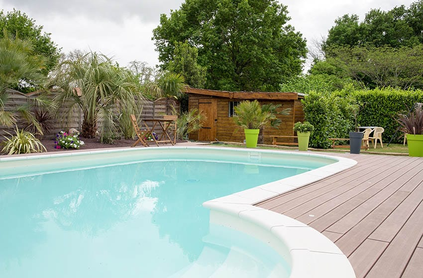 Swimming pool with white plaster finish and wood deck