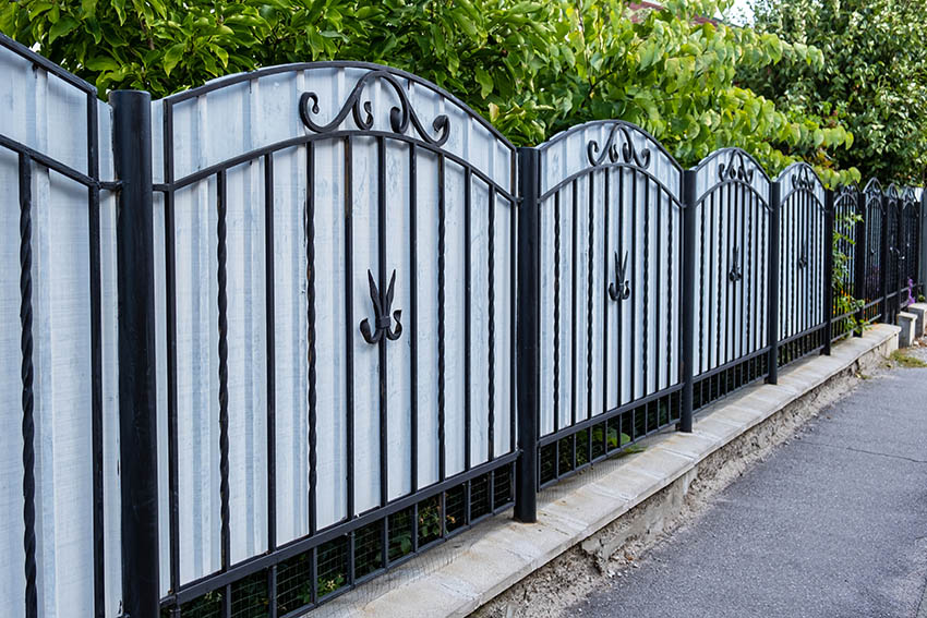 Wrought iron fence with corrugated metal panels