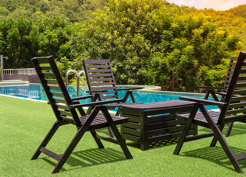 Artificial grass around pool with outdoor chairs and crate table