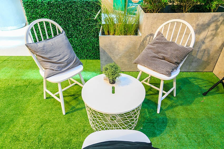 Artificial grass patio with chairs and round table high planter boxes