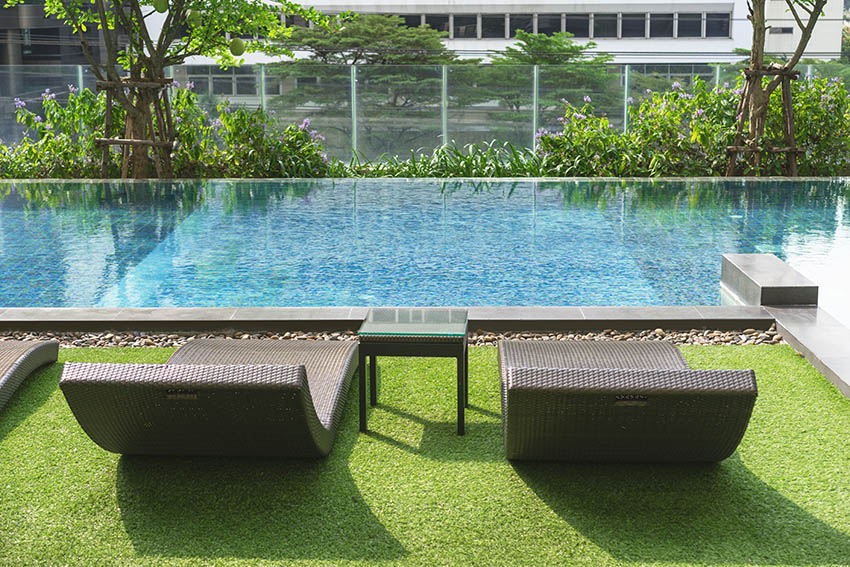 Artificial grass pool deck with lounge chairs