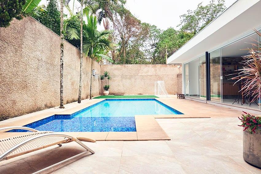 Backyard swimming pool with limestone deck patio