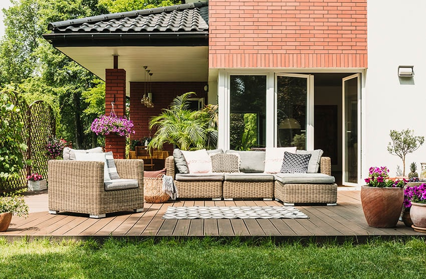 Backyard trex deck with wicker furniture area rug flowering potted plants