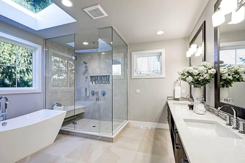 Bathroom with beige porcelain tile shower dark wood vanity arctic white quartz countertop freestanding tub