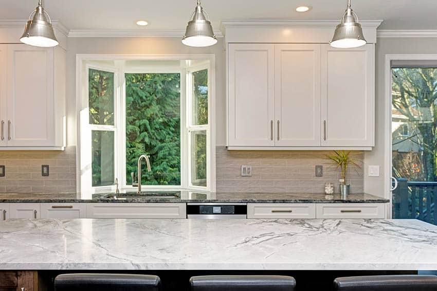 Beautiful kitchen with two tone dekton countertops tile backsplash large island bay window silver pendant lights