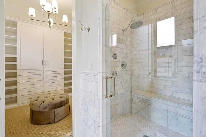 Beautiful walk in shower with marble tile next to large walk in closet