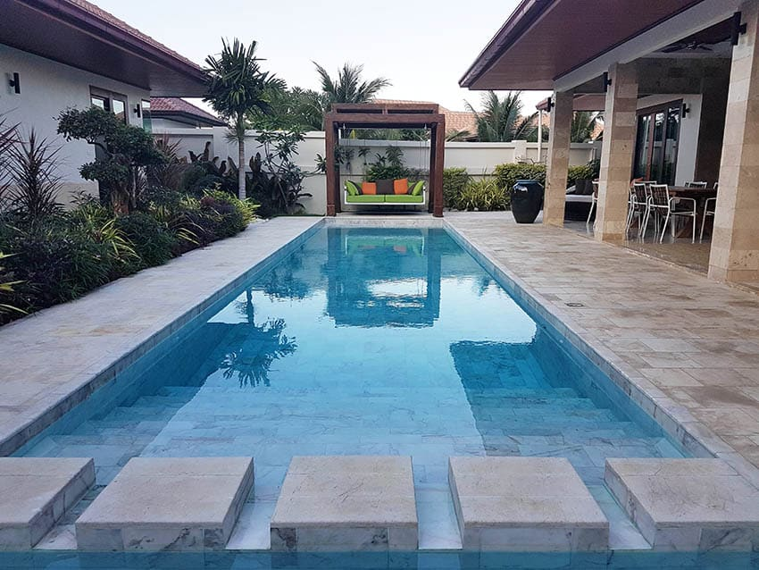 Beige and gray marble pool deck with islands floating day bed covered patio