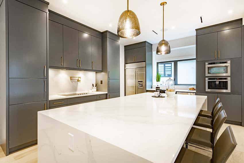 Contemporary kitchen with gray lacquer cabinets gold hardware white quartz countertops gold pendant lights