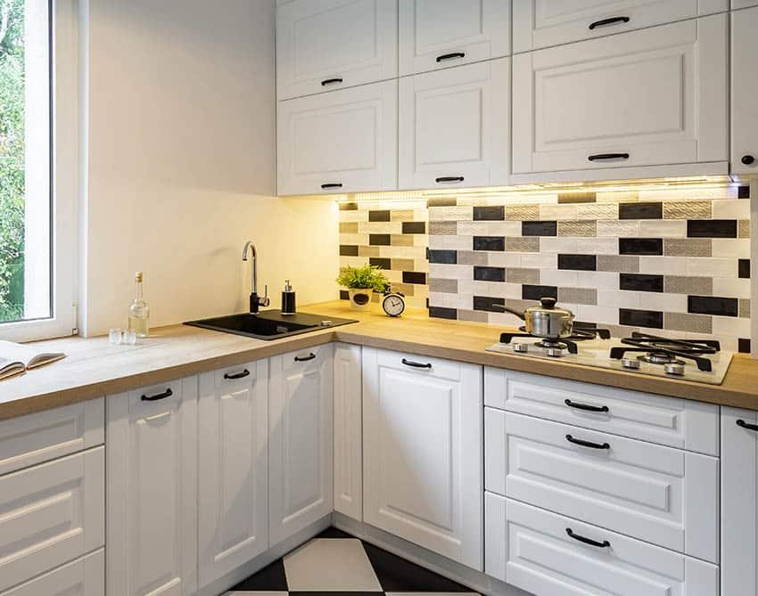 Corner kitchen with black silgranit sink white cabinets butcher block countertops