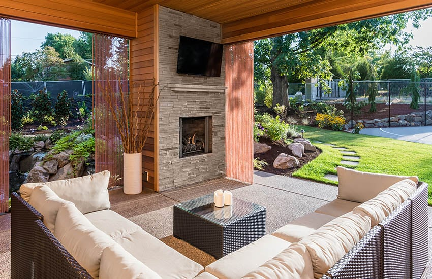 Covered patio with outdoor wind blocking shades wicker furniture stacked stone fireplace