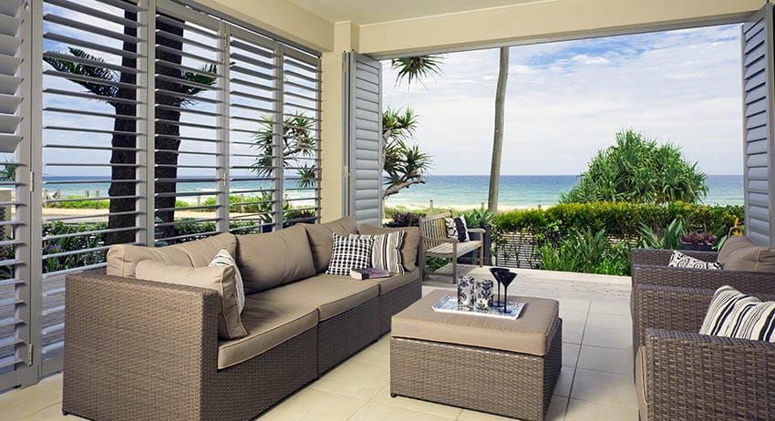 Covered patio with plantation shutters wind block