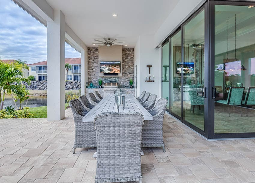 Covered patio with travertine pavers outdoor dining stacked stone fireplace with tv
