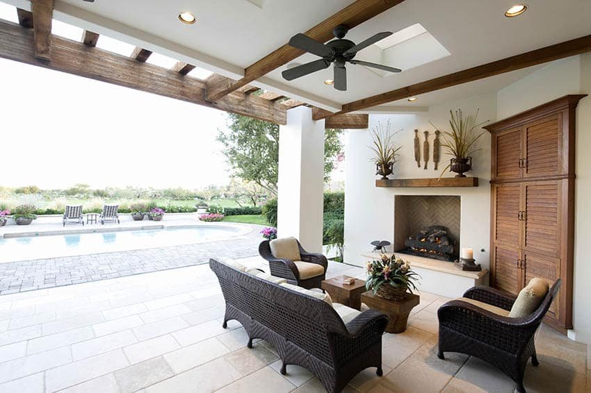 Covered travertine paver patio with outdoor fireplace ceiling fan