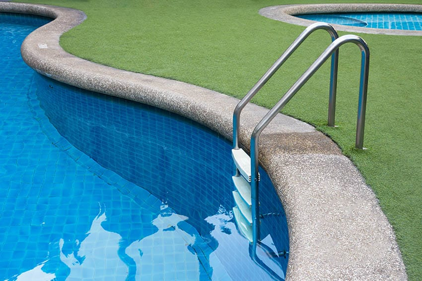 Curved swimming pool with artificial turf patio border