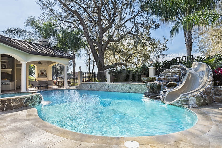 Custom swimming pool with travertine deck water feature waterfall slide