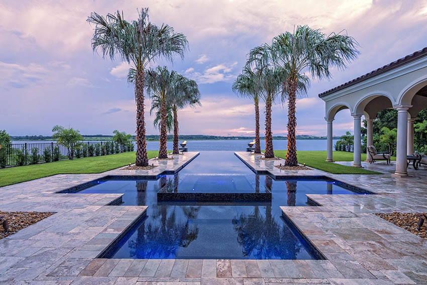 Custom swimming pool with travertine paver deck palm trees water views fire bowls