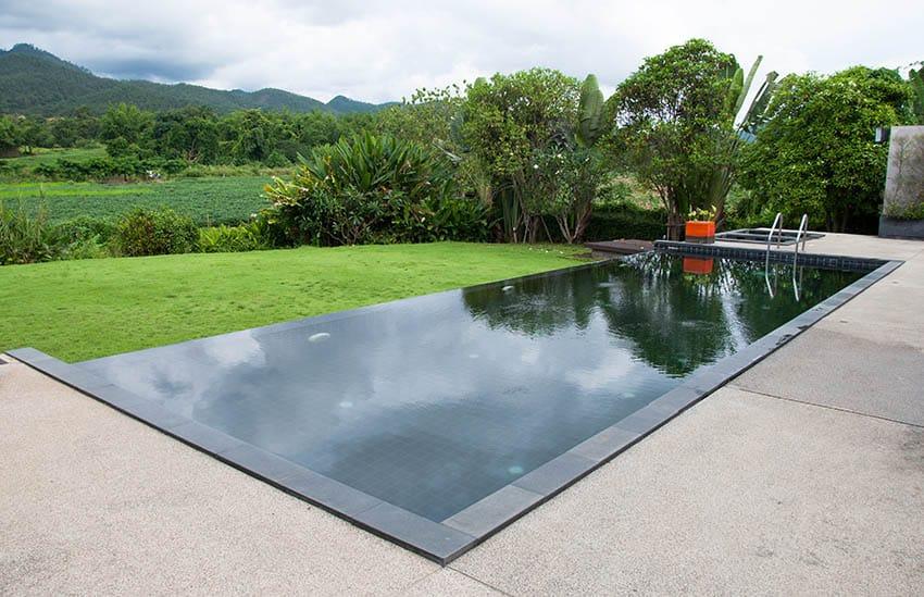 Exposed aggregate pool deck around black bottom pool