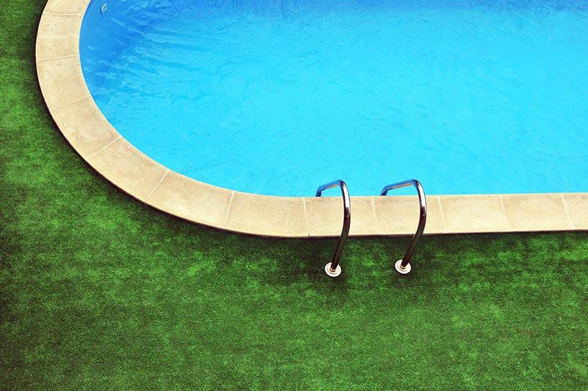 Fake grass patio around oval swimming pool