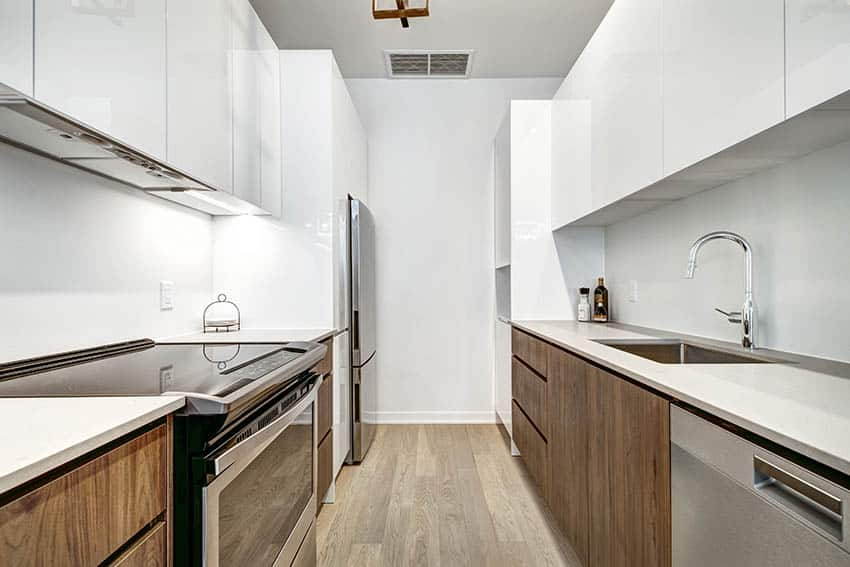 Galley kitchen with white corian countertops wood veneer cabinets