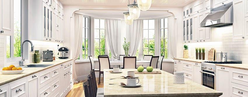 Kitchen with beige dekton countertops raised panel white cabinets