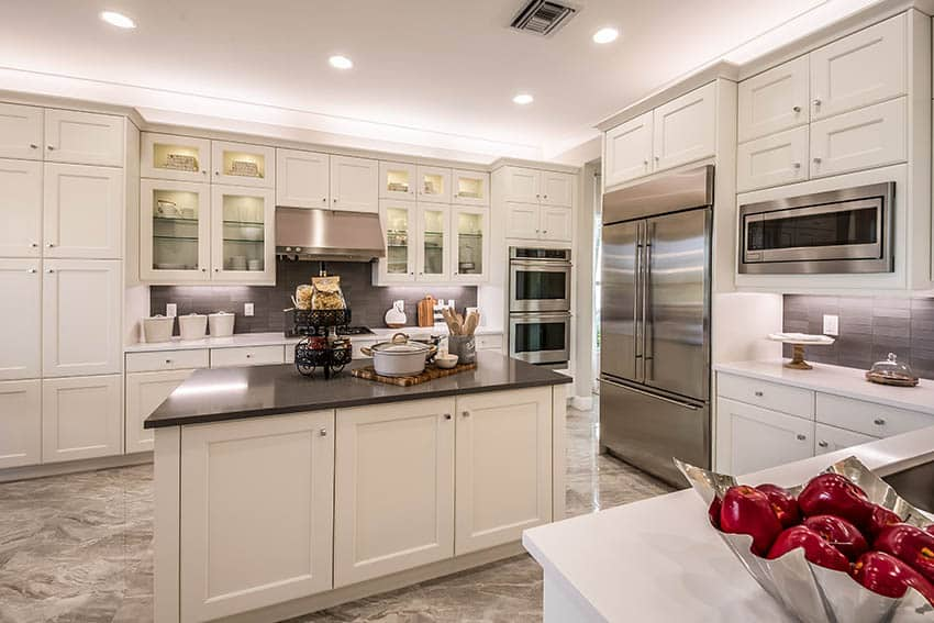 Kitchen with black and white dekton countertops white cabinets recessed lighting