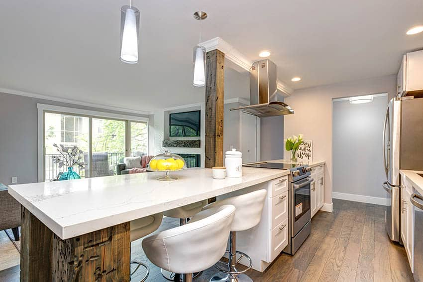 Kitchen with corian countertops reclaimed wood peninsula white shaker cabinets