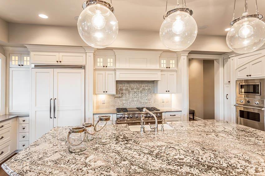 Kitchen with light color granite countertops globe pendant lights