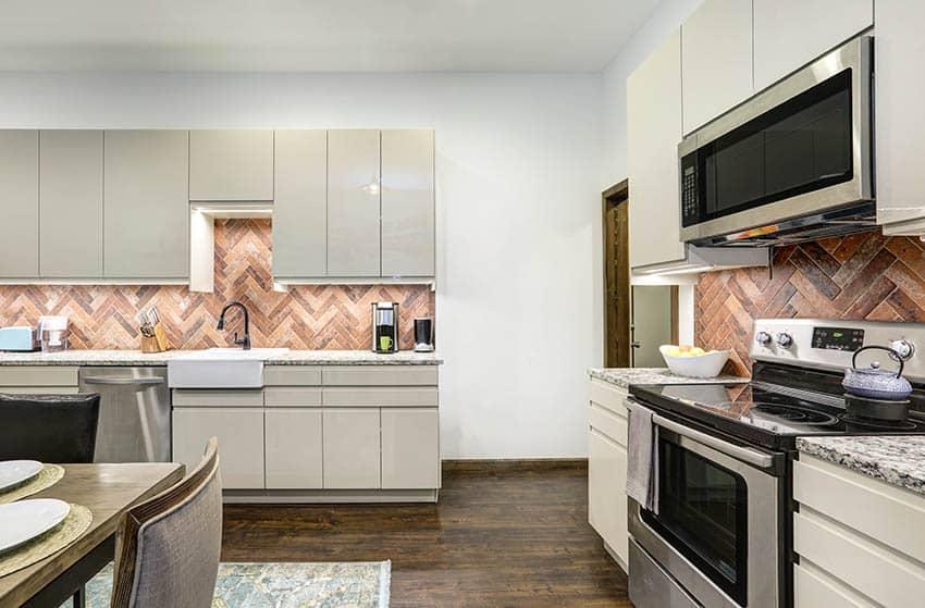Kitchen with light gray lacquer cabinets herringbone pattern brick backsplash wood flooring